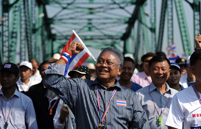 Thai protest leader Suthep Thaugsuban (C) clinches his fist as he leads a protest march through the streets of Bangkok on January 9, 2014 (AFP Photo / Christophe Archambault)