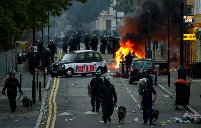 In a file picture taken on August 8, 2011 riot police tackle a mob after a number of cars are set alight in Hackney, north London on the third day of disorder following a protest against the police shooting of Mark Duggan. (AFP Photo / Leon Neal)