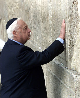 """Prime Minister elect Ariel """"Arik"""" Sharon touches the stones of the Western Wall, also known as the Wailing Wall, as he prays while visiting Judiasm's holiest site in Jerusalem's Old City February 7, 2001.(Reuters / Jwh / aa)"""