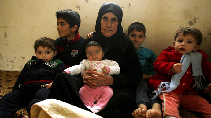 Hallum Al-Amin, a Syrian refugee, sits with members of her family in a house in the village of Qalawayeh, near the southern Lebanese town of Tyre, on January 12, 2014. (AFP Photo / Mahmoud Zayyat)