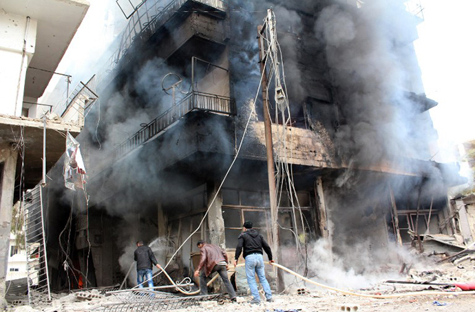 A picture taken on January 12, 2014, shows men trying to put out a fire in a buildings in the city of Daraya, southwest of the capital Damascus. (AFP Photo / Hussam Ayash)