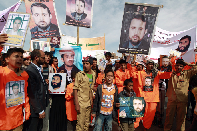 Relatives of Yemeni prisoners being held at the US-run Guantanamo Bay detention camp march in orange jumpsuits while holding their pictures during a demonstration calling for their release outside the US embassy in the capital Sanaa, on January 11, 2014. (AFP Photo / Mohammed Huwais)