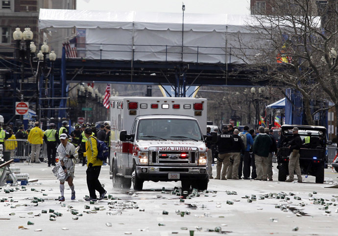 A runner is escorted from the scene after explosions went off at the 117th Boston Marathon in Boston, Massachusetts April 15, 2013. (Reuters/Jessica Rinaldi)