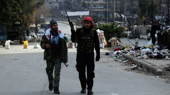 Syrian rebel fighters hold their weapons as they walk along a street in Aleppo's Salaheddine neighbourhood January 10, 2014. REUTERS/Hosam Katan
