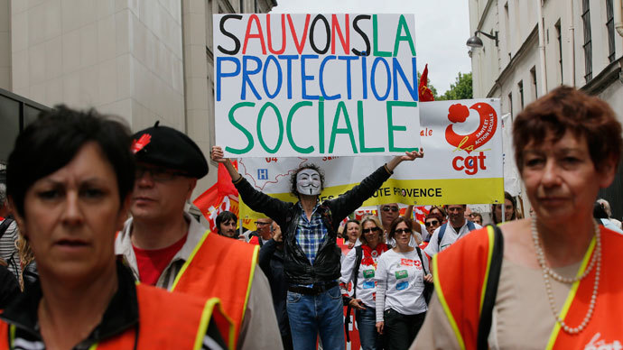A protester wearing a Guy Fawkes mask holds up a placard during a demonstration by health care professionals against the government's austerity reforms in Paris June 15, 2013.(Reuters / Gonzalo Fuentes)
