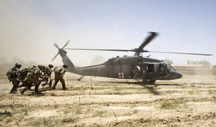 U.S. Army soldiers carry Sgt. Matt Krumwiede, who was wounded by an improvised explosive device (IED), towards a Blackhawk Medevac helicopter in southern Afghanistan in this June 12, 2012 file photo. (Reuters/Shamil Zhumatov)