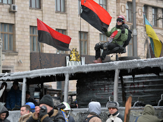 A protester sits on a chair on a burned bus during clashing break of the opposition and the police in Kiev on January 21, 2014. (AFP Photo / Sergei Supinsky)