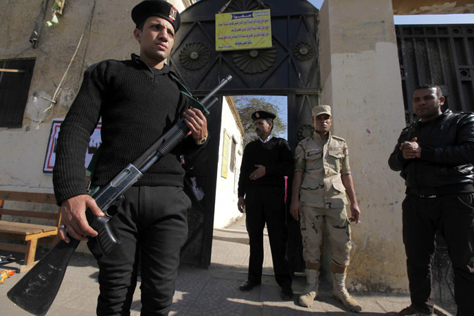 Egyptian police and a soldier stand guard outside a polling station during a referendum on the new constitution in Cairo, January 15, 2014. (Reuters)