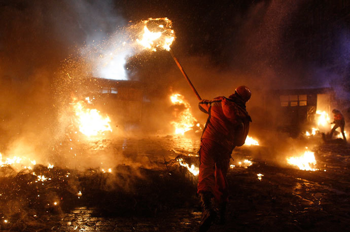 A pro-European protester throws a burning tyre during clashes with riot police in Kiev January 22, 2014.(Reuters / Vasily Fedosenko )