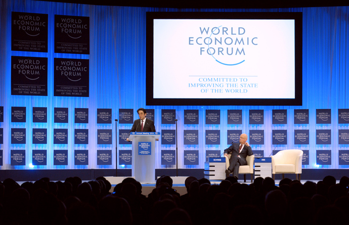Japanese Prime Minister Shinzo Abe speaks as WEF Executive Chairman Klaus Schwab listens during the opening of the plenary session at the World Economic Forum in Davos on January 22, 2014. (AFP Photo / Eric Piermont)