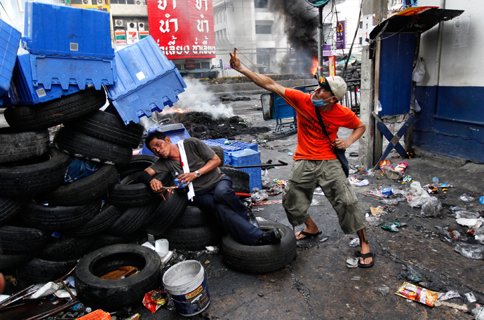 "An anti-government ""red shirt"" supporter aims his slingshot at army soldiers, as his intoxicated comrade lies against a barricade made out of tires, at Rama IV Street in Bangkok May 16, 2010. (Reuters / Jerry Lampen)"