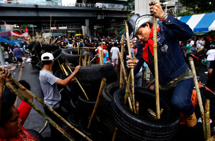 An anti-government 'red shirt' supporter helps dismantle a barricade set in front of Bangkok's Chulalongkorn hospital on May 1, 2010. (Reuters / Jerry Lampen)