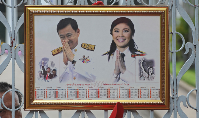 Portrait of ousted premier Thaksin Shinawatra (L) and current Thai Prime Minister Yingluck during a demonstration in front of Parliament House in Bangkok on June 7, 2012. (AFP Photo / Pornchai Kittiwongsakul)