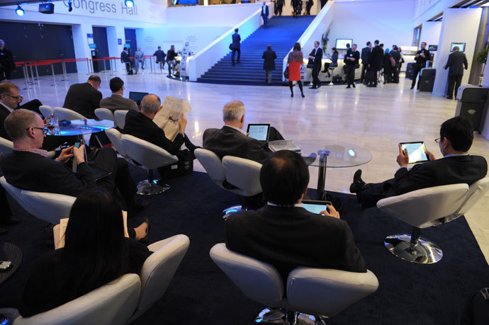 Participants read in the congress center at the World Economic Forum in Davos on January 23, 2014.(AFP Photo / Eric Piermont)