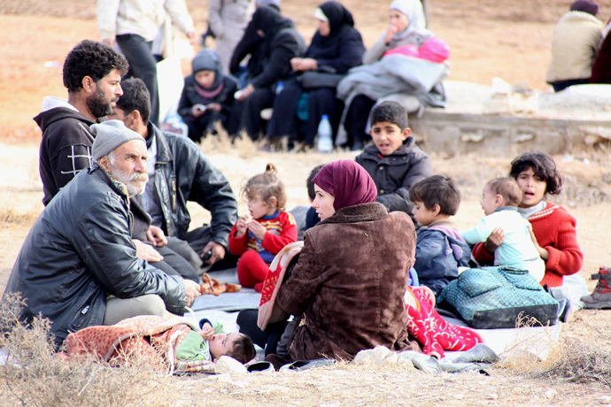 Syrian residents gather after fleeing their homes following clashes between opposition fighters and forces loyal to Syria's President Bashar al-Assad in the Adra area, east of Damascus, in this handout photograph distributed by Syria's national news agency SANA on January 3, 2014. (Reuters / SANA / Handout via Reuters)