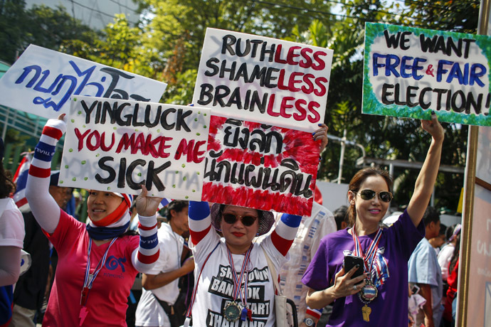 Anti-government protesters hold placards during a march through central Bangkok January 30, 2014. (Reuters/Athit Perawongmetha)