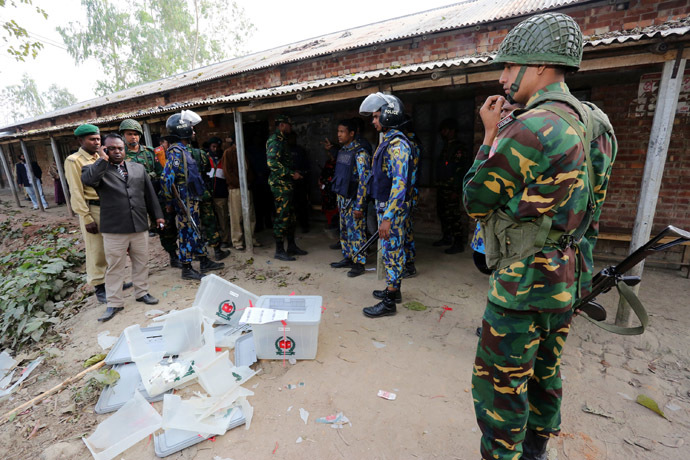 Bangladeshi police and soldiers stand next to damaged ballot boxes in front of a polling station after it was attacked by protestors in the northern town of Bogra on January 5, 2014. (AFP Photo)