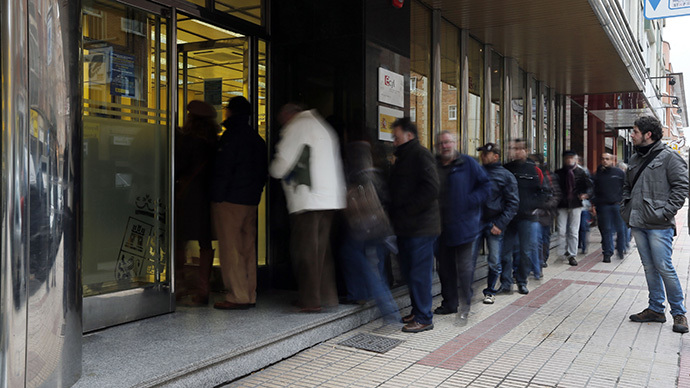 A long exposure photo shows people waiting outside a government employment office in Burgos on February 4, 2013. (AFP Photo / Cesar Manso)