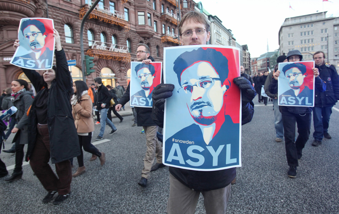 Protestors hold up placards featuring a picture of former NSA contractor Edward Snowden and with the world Asylum on it during a march against the spying methods of the US in Hamburg, northern Germany on December 28, 2013. (AFP Photo / DPA / Bodo Marks)