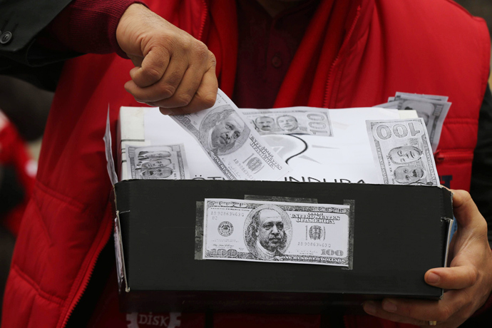 A demonstrator carries a shoe box, a symbol of the corruption scandal after police found $4.5 million secreted in shoe boxes in the home of the chief executive of Turkish state-owned Halkbank, during an anti-corruption protest in Ankara on January 11, 2014. (AFP Photo / Adem Altan)