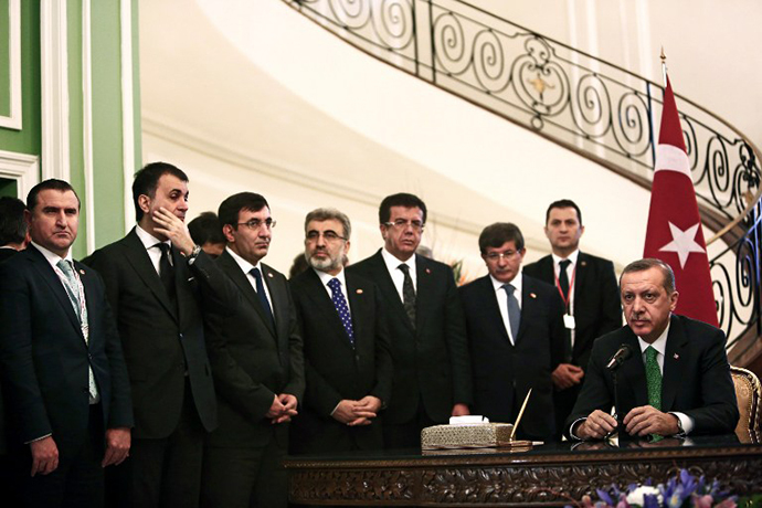 The Turkish delegation stand as Turkish Prime Minister Recep Tayyip Erdogan (R) speaks to the media during a meeting with Iranian officials at Tehran's Saadabad palace on January 29, 2014. (AFP Photo / Behrouz Mehri)