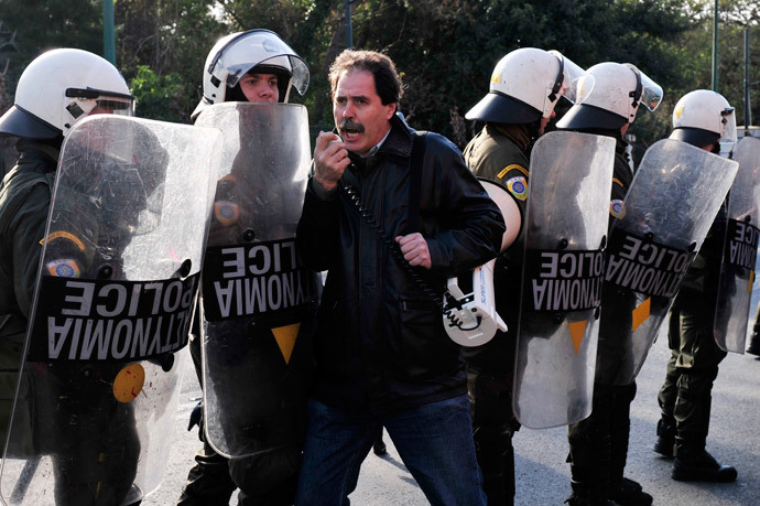 A teacher's union member shouts slogans as police prevent demonstrators to block a road in front of the ministry of administrative reform, during a protest against the civil servant's mobility scheme and layoffs in Athens on January 31, 2014.(AFP Photo / Louisa Gouliamaki )