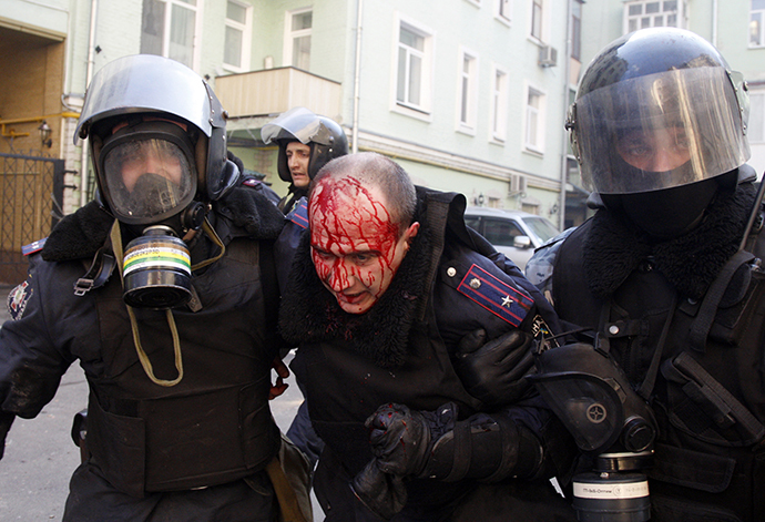 Policeman evacuate a wounded colleague during clashes with anti-government rioters in Kiev on February 18, 2014. (AFP Photo / Anatoliy Stepanov)