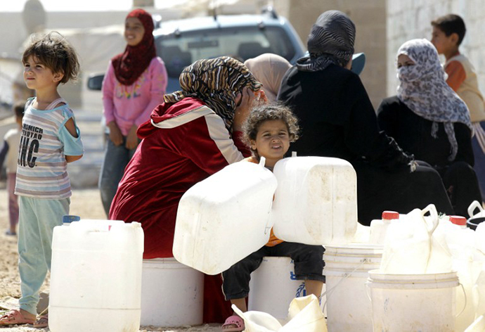 Syrian refugees wait to fill up plastic water containers at the Al-Zaatari refugee camp near the Jordanian city of Mafraq, some 8-kilometres from the Syrian border (AFP Photo / Khalil Mazraawi)