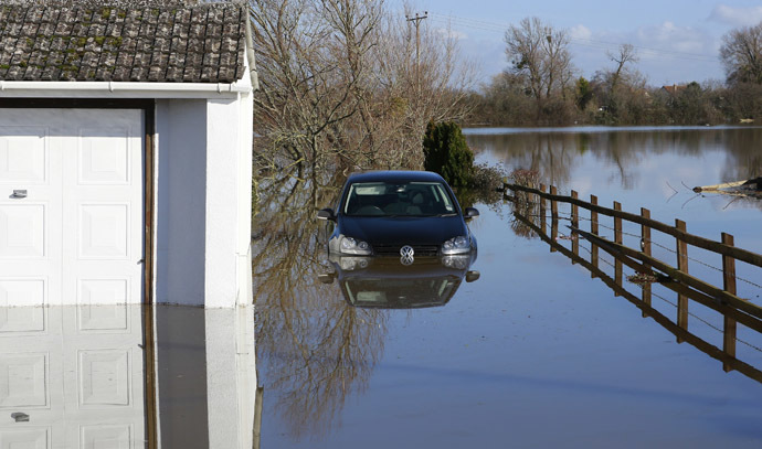 A semi-submerged car is seen in urban landscape taken in the flooded Somerset village of Moorland February 16, 2014. (Reuters)