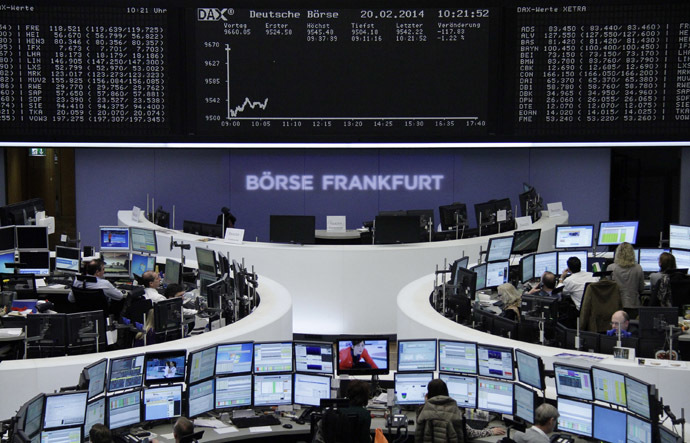 Traders are pictured at their desks in front of the DAX board at the Frankfurt stock exchange (Reuters)