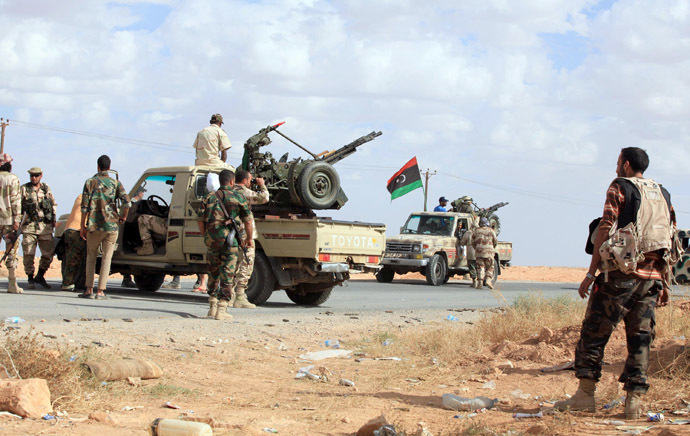 """Pro-government fighters gather on October 23, 2012, one kilometer from the northern entrance to the town of Bani Walid, one of the final bastions of Moamer Kadhafi's ousted regime, as Libya celebrates the first anniversary of its """"liberation"""" from the regime, even as fighting flared in a former bastion of the slain dictator. (AFP Photo)"""