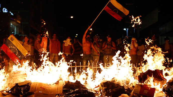 Opposition demonstrators hold a Venezuelan flag in front of a burning barricade during a protest against President Nicolas Maduro's government in Caracas February 15, 2014 (Reuters / Carlos Garcia Rawlins)