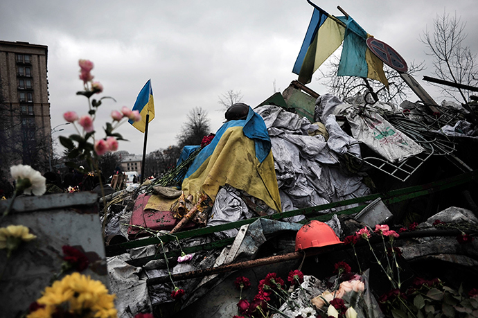 Flags, flowers and a helmet are left on a barricade in central Kiev in homage to demonstrators killed during last week's clashes in central Kiev on February 25, 2014 (AFP Photo / Louisa Gouliamaki)