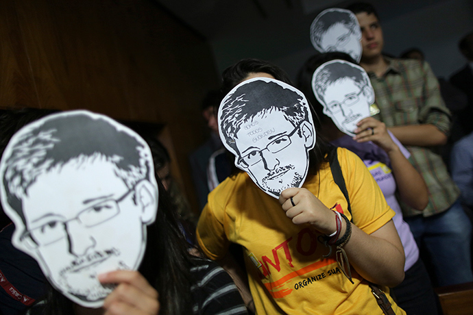 People use masks with pictures of former NSA contractor Edward Snowden masks (Reuters / Ueslei Marcelino)