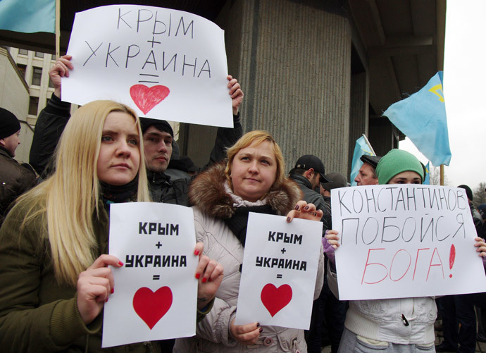 """Pro-Ukrainian activists hold placards reading """"Crimea+Ukraine is love"""" during a rally in front of the Crimean parliament in Semfiropol on February 26, 2014. (AFP Photo / Vasiliy Batanov)"""