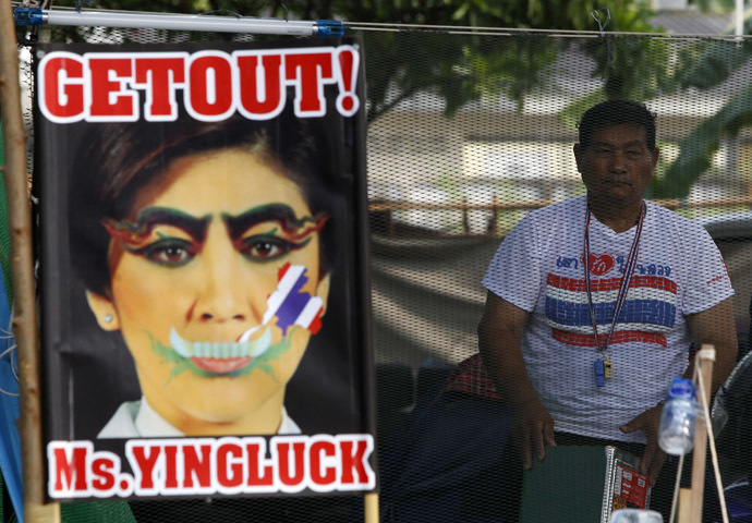 An anti-government protester stands next to a defaced image of Thailand's Prime Minister Yingluck Shinawatra during a rally near the Government Complex in Bangkok February 18, 2014. (Reuters)