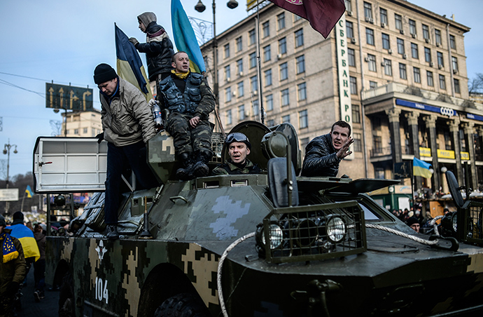 Protestors stand on a military armoured vehicle in central Kiev on February 26, 2014 (AFP Photo / Bulent Kilic)