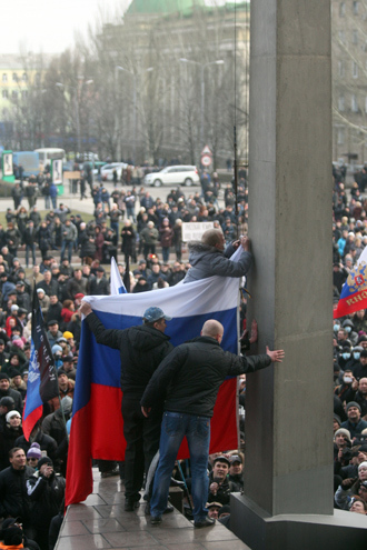 Pro-Russian protesters raise a Russian flag in front of the regional administration building during a rally in the industrial Ukrainian city of Donetsk on March 1, 2014 (AFP Photo / Alexander Khudoteply)