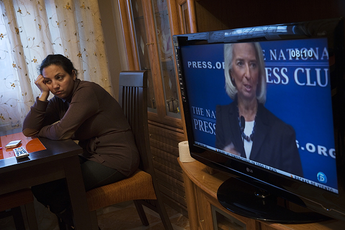 IMF Chief Christine Lagarde is seen on TV as Eva Borja Jimenez waits for the judicial commission to carry out her eviction in Madrid (Reuters / Susana Vera)