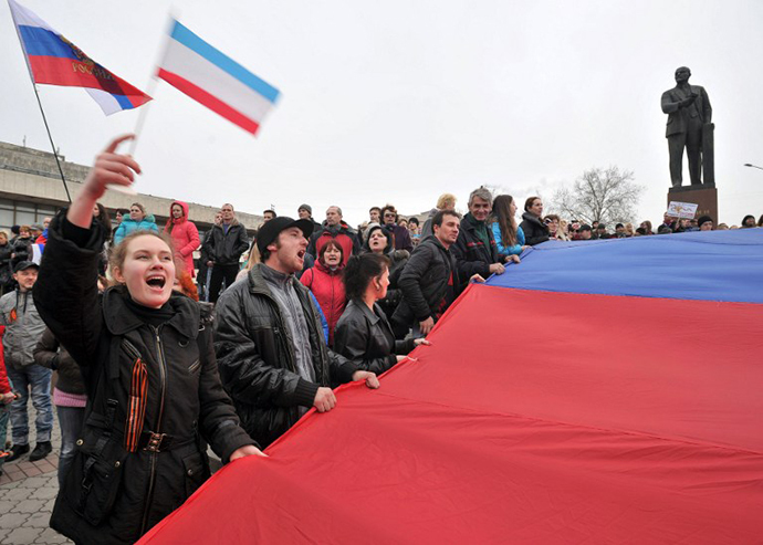 Pro-Russian activists hold a giant Russian flag near a statue of Lenin as they rally in Simferopol, the administrative center of Crimea, on March 1, 2014. (AFP Photo / Genya Savilov)