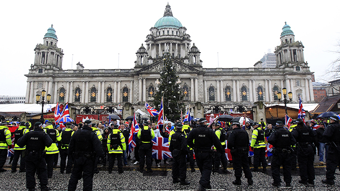 Police in riot gear look on as protesters wave Union Flags in front of the City Hall provoked by a decision to remove the British flag from Belfast's City Hall (Reuters / Cathal McNaughton)