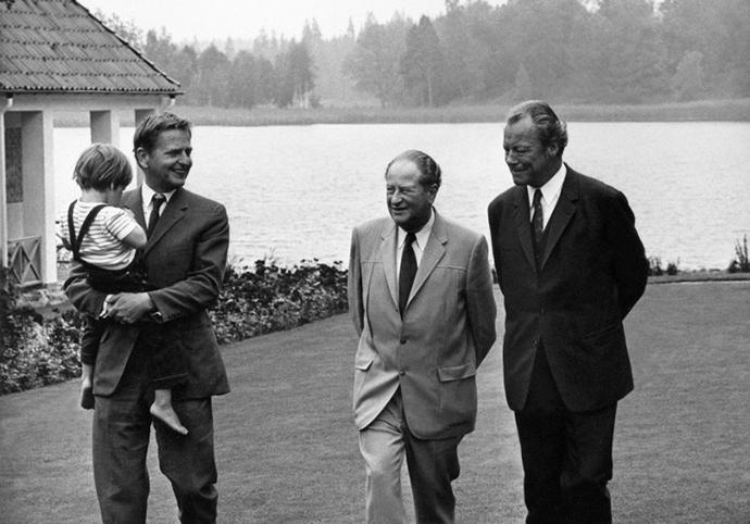 Swedish Prime Minister, Olof Palme (L), carries his child, walking in his Harpsund's property in Sweden, with Bruno Kreisky, Austrian chancellor (C) and his West German counterpart Willy Brandt (R), 04 August 1971. (AFP Photo)