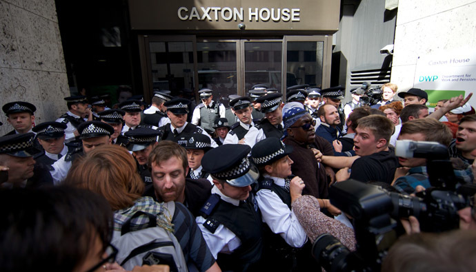 Ranks of police officers disperse protesters against multinational IT firm and Paralympics sponsor Atos from outside the offices of the Department of Work and Pensions in London on August 31, 2012. (AFP Photo)