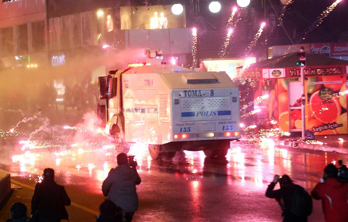 Fireworks thrown by protesters explode near a police water cannon truck as police officers disperse a rally against Turkey's Prime Minister Recep Tayyip Erdogan in Ankara, on March 1, 2014. (AFP Photo / Adem Altan)