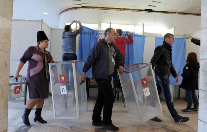Employees carry ballot boxes as the others prepare the polling booth in one of the polling stations of Sevastopol on March 15, 2014, on the eve of the referendum in Crimea. (AFP Photo / Viktor Drachev)