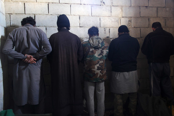Fighters from the Islamic State in Iraq and the Levant (ISIL) are seen detained by the Free Syrian Army fighters (unseen) after the FSA captured their base in the countryside of Hama January 9, 2014. (Reuters / Omran Morad)