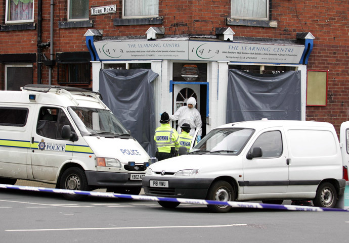 Policemen talk to a forensic expert on the steps of an Islamic bookshop that was raided as part of a fast moving investigation into the London bombings on Bude Road in Leeds, 18 July 2005. (AFP Photo / Steve Parkin)