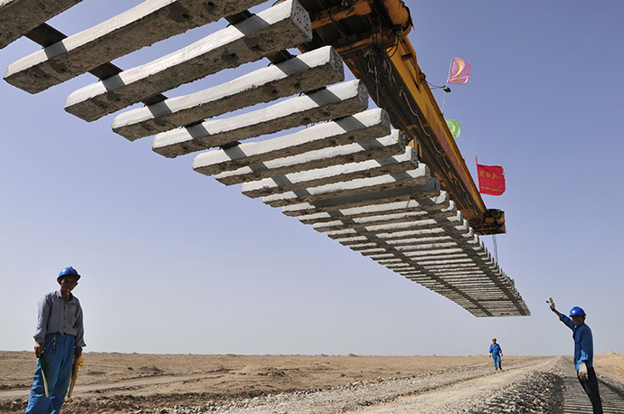 Workers direct a crane to lay a segment of tracks on the Kumul-Lop Nor line's railway bed in Lop Nor, Xinjiang Uighur Autonomous Region July 15, 2012. (Reuters / Rooney Chen)
