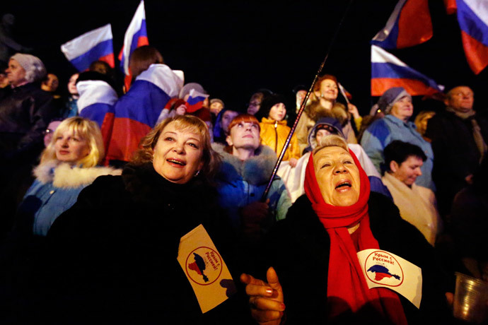 "Two women hold flags reading ""Crimea is with Russia"" as people wait for the announcement of preliminary results of today's referendum on Lenin Square in the Crimean capital of Simferopol March 16, 2014.(Reuters / Thomas Peter)"