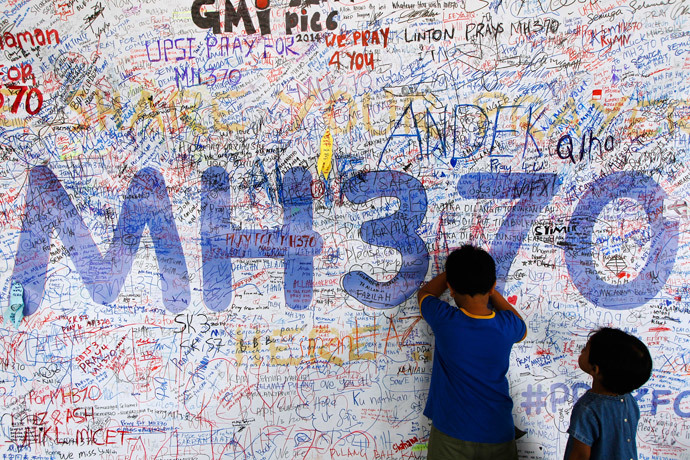 Children write well-wishes on a banner for the passengers and crew of the missing Malaysia Airlines Flight MH370 at a viewing gallery in Kuala Lumpur International Airport March 19, 2014.(Reuters / Edgar Su)